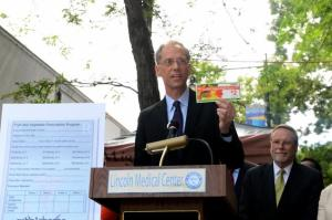 "Thomas Farley, city health commissioner, holds up one of the coupons that doctors can ""prescribe"" to encourage patients to eat more fruits and vegetables."